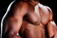 Close up of very muscular torso of an african american body builder.