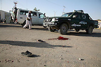 The hat and shoes of a teenage boy lie next to a pool of blood after he was hit by a rocket that landed near the main polling station in the Helmand capital of Lashkar Gah. The boy later died.