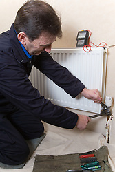 Gas man using pliers to unscrew a radiator valve,
