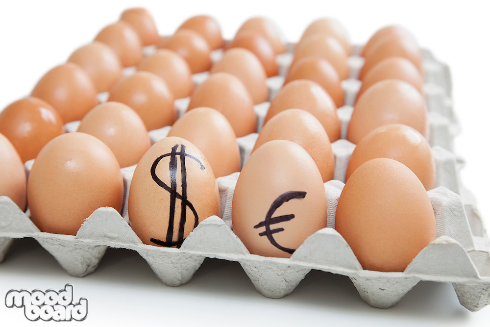 Brown eggs in carton with dollar and euro sign over white background