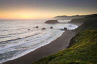 Sunset view of surf beaches and Goat Rock from rugged cliffs and bluffs of Sonoma Coast State Park, California