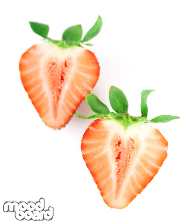 Halved strawberries on white background