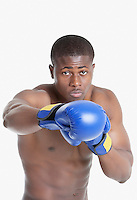 Portrait of an African American boxer punching over gray background