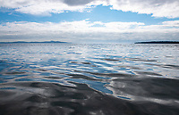 Marine clouds on a summer day are reflected in the ocean water in Cordova Bay, in Victoria, BC