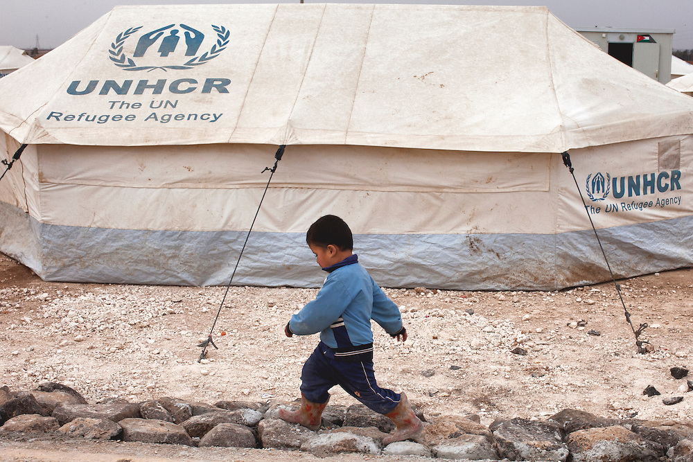 "A young boy walks past a UNHCR (United Nations High Commissioner for Refugees) tent. In the early days of Zaatari these tents dominated the landscape of the camp. They are slowly being replaced with prefabricated structures dubbed ""Caravans."" Jan. 27, 2014. Zaatari Camp, Jordan. (Photo by Gabriel Romero/Alexia Foundation ©2014)"