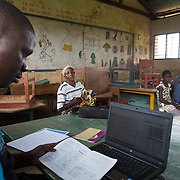 Data clerk Oscar Kai enters medical information into his computer at an outreach clinic at the Ngamani Primary School. Moms bring their children for routine check-ups and vaccinations and Oscar enters patient information into his computer about the PCV 10 vaccine, as well as pentavalent, BCG, polio, yellow fever, measles, diphtheria, tetanus and hepatitis B immunizations. All of that information is then uploaded to portable hard-drives that are returned weekly to the study headquarters, where the database is updated.<br /> <br /> &quot;Because the database is digitized, it means it's far easier to keep our records fresh, even if children move and access health services in different locations,&quot; says Dr. Benjamin Tsofa, the Kenyan health ministry's chief liaison on the study. <br /> <br /> In January 2011, the Kenyan government with support from the GAVI Alliance, introduced a new vaccine, PCV-10, which targets 10 bacteria than can cause Invasive Pneumococcal Disease.The vaccine's impact is monitored through an electronic database, part of the GAVI funded PCV impact study, which maps the growing coverage of the new vaccine. Already, here in Kilifi, the incidence of the illness in children aged five has gone down by approximately two-thirds.