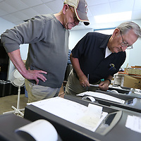 Mike Maynard and Chuck Young, look over the voting machines during a voting machine test at the Circuit Clerk's Office in advance of the primary election in Tupelo.