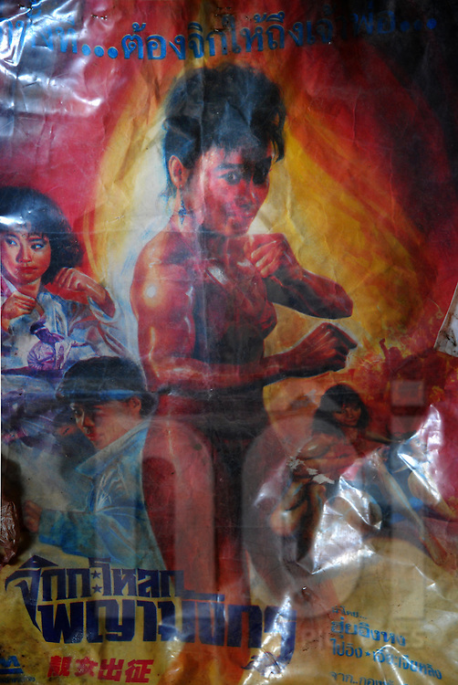 Old Kung Fu movie poster starring women fighters hanging on a wall in the abandoned Bouasavanh cinema in Vientiane, Laos, Southeast Asia