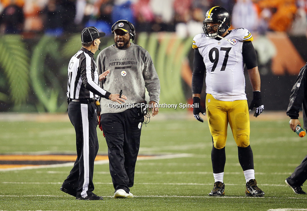 NFL line judge Ron Marinucci (107) talks to Pittsburgh Steelers head coach Mike Tomlin after Cincinnati Bengals running back Giovani Bernard (25) gets hit hard by Pittsburgh Steelers inside linebacker Ryan Shazier (50) causing a third quarter fumble, recovered by Shazier, and starting a player melee over no penalty call for unnecessary roughness and leading with the helmet during the NFL AFC Wild Card playoff football game against the Pittsburgh Steelers on Saturday, Jan. 9, 2016 in Cincinnati. The Steelers won the game 18-16. (©Paul Anthony Spinelli)
