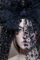Close-up portrait of a young woman wearing black veil