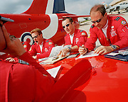 Pilots the 'Red Arrows', Britain's Royal Air Force aerobatic team during pre-flight briefing 'on the wing' before display.
