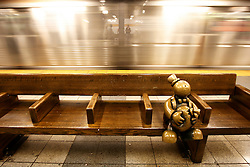 A train goes past a sculpture of a man with a money bag sitting in a subway station by Tom Otterness in New York, New York, USA, 23 October 2008. As Wall Street descend into a financial turmoil not seen since the stock market crash of 1929 and financial businesses were pommeled into rampant sell-offs in stocks and face regulatory changes to their business practices, professionals and non-professionals working in the district's banks, stock-trading houses and insurance companies are showing stress and a gloom not unlike the times of the Great Depression.