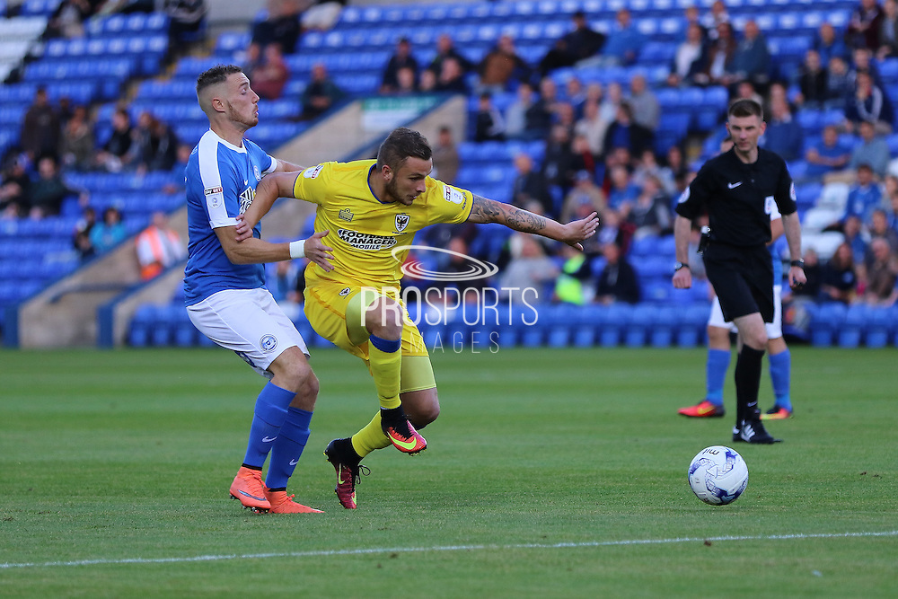 AFC Wimbledon midfielder Dean Parrett (18) and Peterborough United striker Marcus Maddision (11) during the EFL Cup match between Peterborough United and AFC Wimbledon at ABAX Stadium, Peterborough, England on 9 August 2016. Photo by Stuart Butcher.