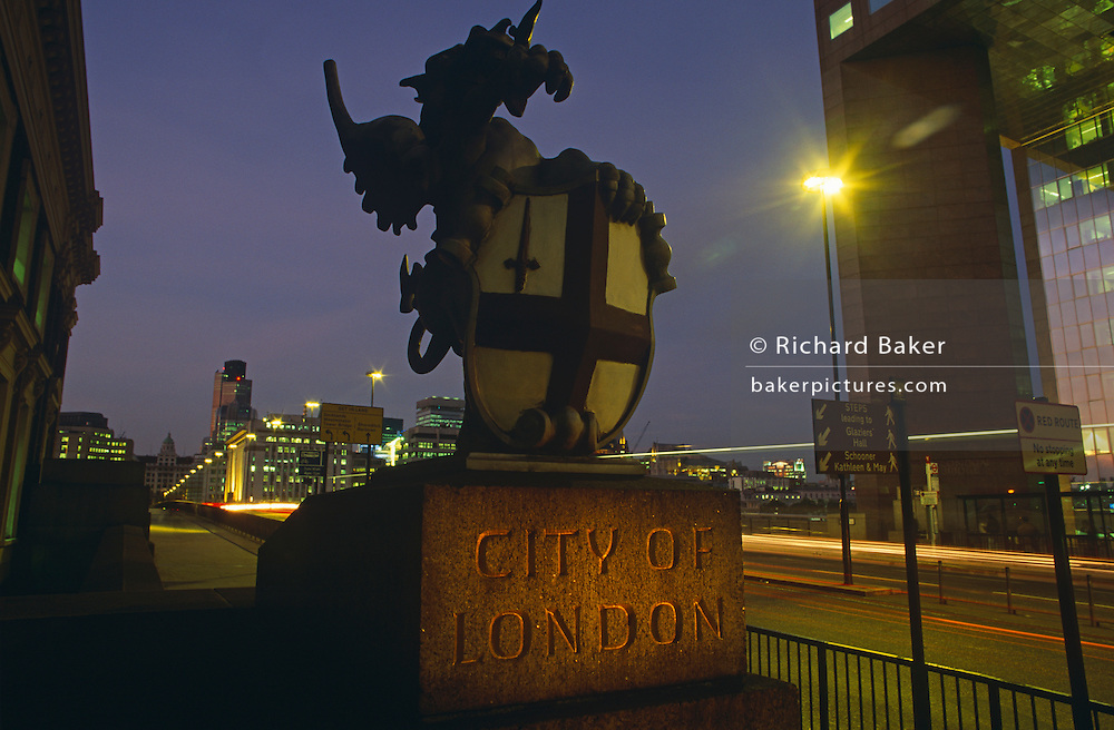 As traffic drives over London Bridge, a griffin statue marks the southern boundary between Southwark on the south side and the City of London beyond on the bridge. The City of London is a geographically-small City within Greater London, England. The City of London is the historic core of London from which, along with Westminster, the modern conurbation grew. The City's boundaries have remained constant since the Middle Ages but  it is now only a tiny part of Greater London. The City of London is a major financial centre, often referred to as just the City or as the Square Mile, as it is approximately one square mile (2.6 km) in area. London Bridge's history stretches back to the first crossing over Roman Londinium, close to this site and subsequent wooden and stone bridges have helped modern London become a financial success.