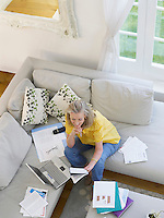 Woman using laptop sitting on sofa elevated view