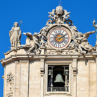 Clock Tower at St. Peter&rsquo;s Basilica in Rome, Italy <br /> Flanking both sides of St. Peter&rsquo;s Basilica are two towers. On top is the coat of arms for the city-state of Vatican City.  Beneath it is a clock with Roman numerals held by two angels. And then you&rsquo;ll notice the bells, the oldest of which was cast in 1288.