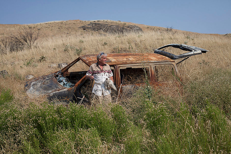 Mark Nelson poses for a portrait with his cat, Fluffy, in the location that he crashed his van while fleeing the Carlton Complex near Brewster, Washington on July 9, 2015.