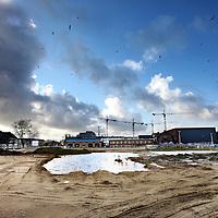 Nederland, Amsterdam , 23 januari 2012..Het nieuwe woon- werkgebied Oostpoort gezien vanaf het voormalige dierenasiel en huidige kraakpand. Momenteel is het slechts nog een zandvlakte wachtend op de juiste bestemming. Op de achtergrond het muziek gebouw MuzyQ (r)..Foto:Jean-Pierre Jans