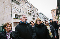 """NAPLES, ITALY - 2 FEBRUARY 2019: Passengers of the literary bus tour """"Neapolitan Novels"""" liste to their guide during a visit in the Rione Luzzatti, the neighborhood in which Elena Ferrante's """"My Brilliant Friend"""" is set, in Naples, Italy, on February 2nd 2019.<br /> <br /> In December 2018, City Sightseeing - the world's largest sightseeing tour bus operator - inaugurated the """"Brilliant Naples"""" tour, inspired by the locations in """"Neapolitan Novels"""", a 4-part series by the Italian novelist Elena Ferrante. The series has sold over 10 million copies in 40 countries. The first book in the series has also been adapted into an HBO television series entitled, """"My Brilliant Friend."""""""