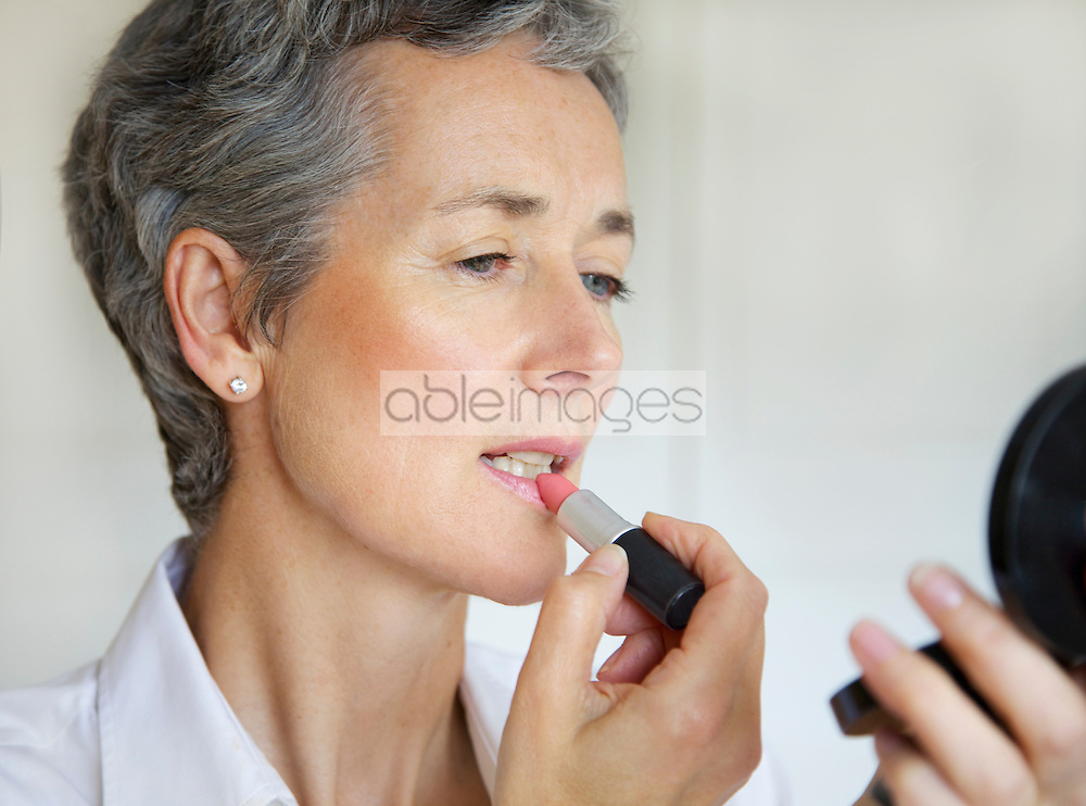 Woman Holding Compact Mirror Applying Lipstick