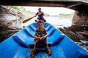 Abah Dayat and his grandson Fazril on the Citarum River collecting scraps. Citeureup Village, Kabupaten Bandung.  ..Credit: Andri Tambunan for Greenpeace