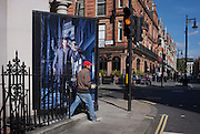 A workman steps on to street level in front of a construction hoarding featuring a male with a bird of prey on his arm, in Mayfair, central London, England.