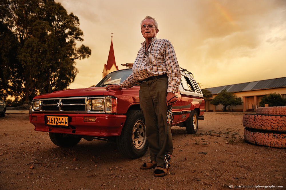 (2008) Father Hermann poses with his old Toyota in front of the roman catholic church at Pioneers Park, where his home, a two room apartment, is located. He always has a big key chain with him, because he has to lock everything tp prevent it from getting stolen.