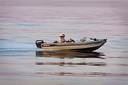 Two fishermen head home after a day out on the Mississippi River, speeding south at Sabula, IA.