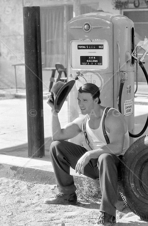 man dressed in 40's clothing sitting by an old gas station in California