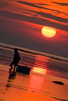 Balinese fisherman silhouetted by a firey rising sun