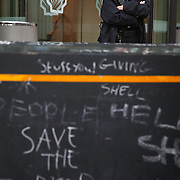 Graffiti on the security fence outside Shell's London HQ. The giant polar bear puppet Aurora made by Greenpeace walked the streets of London in defence of the Arctic as part of a Greenpeace global day of action. The parade,part performance part protest, was to highlight the melting ice caps and the increasing and potentially devastating oil drilling in the arctic sea. Shell is one of the companies drilling and the march through London ended up outside Shell London HQ to draw attention to their oil business in the arctic. Aurora, the biggest polar bear in the world represents all endangered species in arctic.