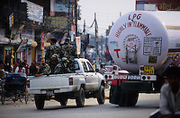 Nepalganj, 24 February 2005.  Royal Nepal Army escorting a lorry load of Liquefied Petroleum Gas durind a nationwide transport blockade called by the Maoist. During those stoppages, vehicles are escorted by the RNA. In some occasions the Military have confiscated the vehicles from drivers who refused to drive in or out the cities. The Maoist have destroyed buses and an ambulance driven during the blockade, they have also shot dead an Indian driver while under military escort.
