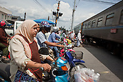 """Sept. 26, 2009 -- YALA, THAILAND: Thais wait for a train to clear a crossing in Yala, Thailand. Thailand's three southern most provinces; Yala, Pattani and Narathiwat are often called """"restive"""" and a decades long Muslim insurgency has gained traction recently. Nearly 4,000 people have been killed since 2004. The three southern provinces are under emergency control and there are more than 60,000 Thai military, police and paramilitary militia forces trying to keep the peace battling insurgents who favor car bombs and assassination.  Photo by Jack Kurtz / ZUMA Press"""