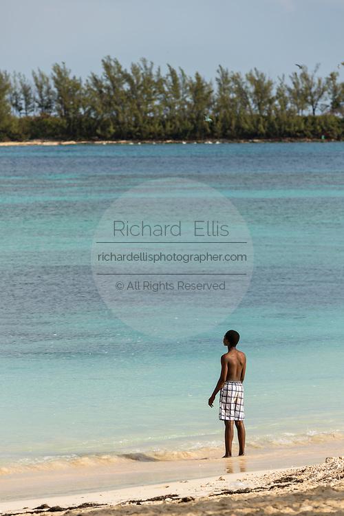 Young boy along on the beach Junkanoo Beach in Nassau, Bahamas