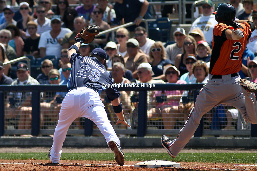 March 20, 2011; Port Charlotte, FL, USA; Baltimore Orioles shortstop J.J. Hardy (2) reaches first base safely for a one run single as Tampa Bay Rays first baseman Dan Johnson (29) is pulled off the bag by a wide throw during a spring training exhibition game at Charlotte Sports Park.   Mandatory Credit: Derick E. Hingle
