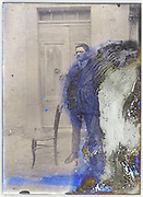 severely eroding glass plate with an adult man standing with chair in front of closed door