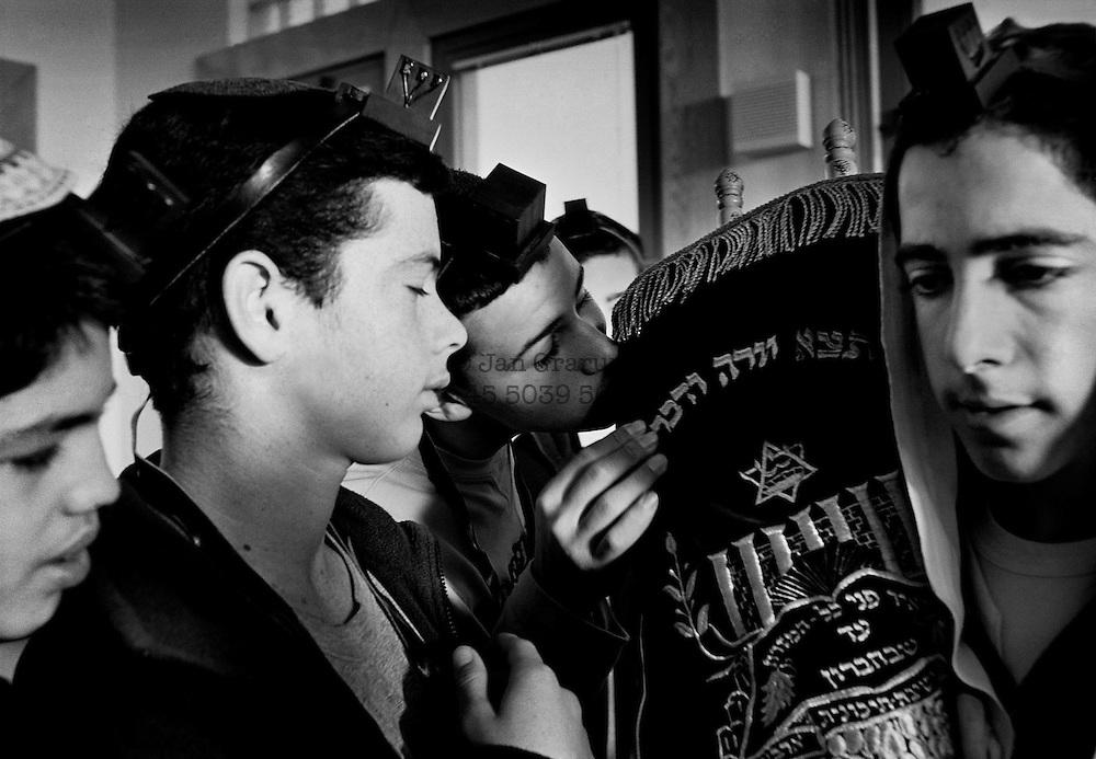 The schoolboys kiss the Torah scrolls carried through the yeshiva in Kiriyat Arba.  Hebron 2001.