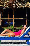 Woman sunbathing by a beach bungalow, Belize