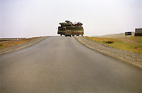 On the road to Kandahar a passeger's bus, loaded with a car and a trak on its roof, travel towards Kabul.