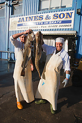 Fishmongers holding up cod outside their premises