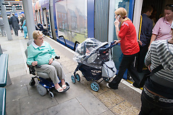 Woman wheelchair user approaching the tram,