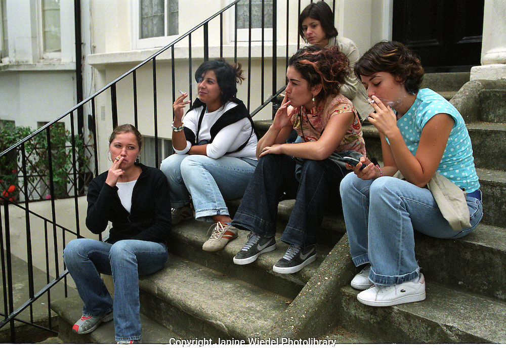 Group of young women sitting outside on steps of the house smoking cigarettes.
