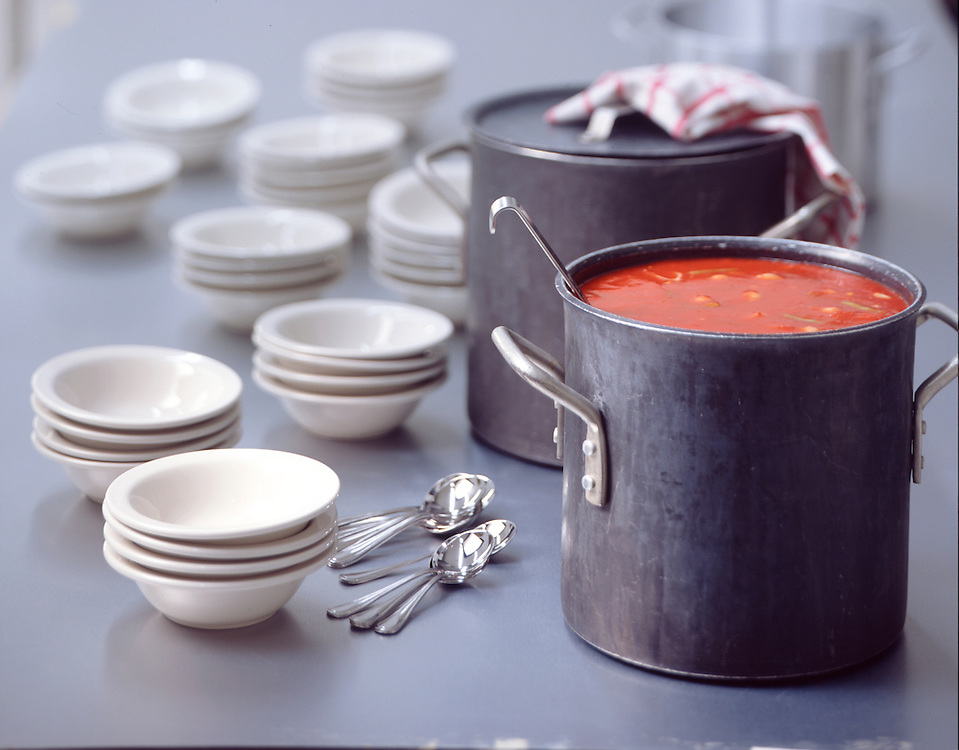 Large pots of soup and soup bowls are spread out on a countertop for serving.