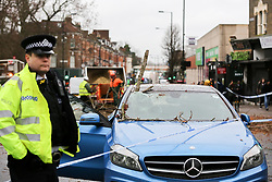 © Licensed to London News Pictures. 12/03/2019. London, UK. A branch of the tree sticks out from the Mercedes' front windscreen and damaged the front and the back windscreens.<br /> A tree has fallen on Green Lanes in Haringey, North London due to strong winds. Green Lanes is closed between Manor House underground station and Endymion Road. Met Office is warning to prepare for rain and 80mph gales as Storm Gareth hits later today bringing the risk of heavy flooding. Photo credit: Dinendra Haria/LNP