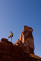 A young woman admires the view from the flanks of Castleton Tower near Moab, Utah.