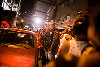A UPP officer stands guard watching over Rocinha residents, the biggest favela in Brazil, with over 100,000 residents, in Rio de Janeiro, Br., on Thursday, Jan. 24, 2013. In early November 2011 about 3,000 police officers and soldiers moved into one of the largest slums in Latin America in an effort by the Brazilian government to assert control over lawless areas of the city ahead of the 2014 World Cup and 2016 Summer Olympics.