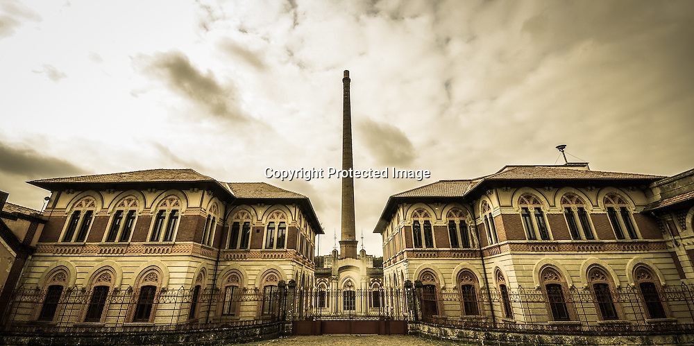 Factory with chimney at historic industrial town Crespi d'Adda near Bergamo, Lombardy, Italy