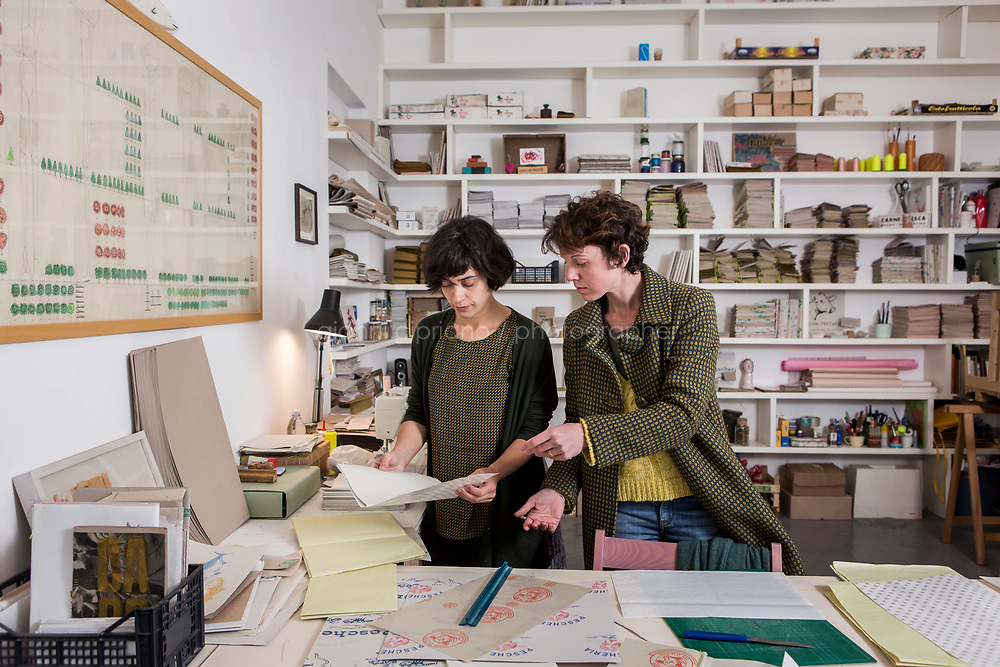 PALERMO, ITALY - 8 MARCH 2017: (L-R) Architect and designer Carmela Dacchille, founder of Edizioni Precarie, and her coworker Giulia Basile, are seen here at work at the Edizioni Precarie workshop, which recovers paper, formerly used to wrap food in the historical markets of the city, to make notebooks for expressing thoughts, in Palermo, Italy, on March 8th 2017.