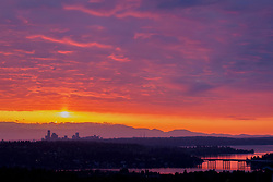 North America, United States, Washington. Lake Washington, Mercer Island, Seattle skyline, and Olympic mountains viewed from Bellevue at sunset.
