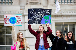 © Licensed to London News Pictures. 15/03/2019. LONDON, UK.  Students hold up signs on Whitehall. Thousands of students take part in a Climate Change strike in Parliament Square, marching down Whitehall to Buckingham Palace.  Similar strikes by students are taking part around the world demanding that governments take action against the effects of climate change.  Photo credit: Stephen Chung/LNP